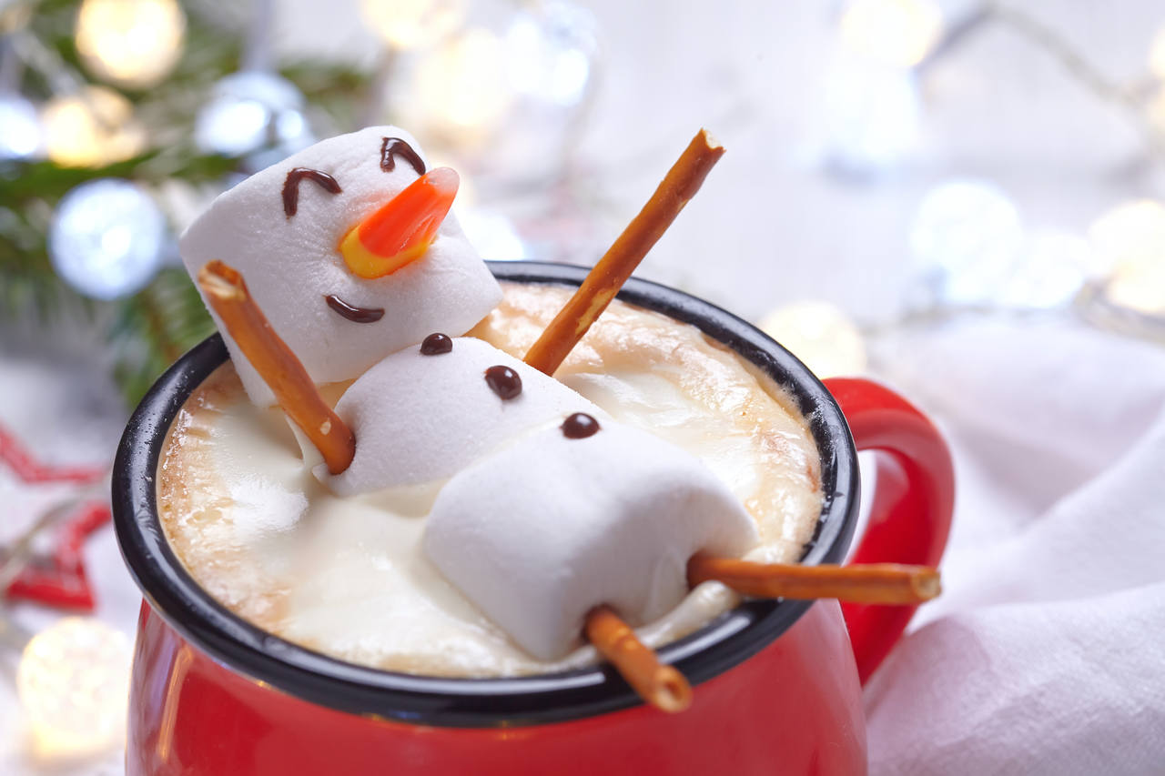 marshmallow snowman floating in a cup of hot chocolate