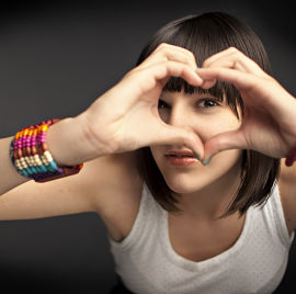 teenaged girl making a heart with her hands, on grey background