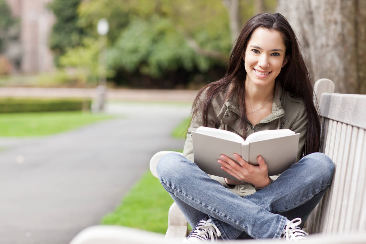 Girl Sitting On Bench with Open Book