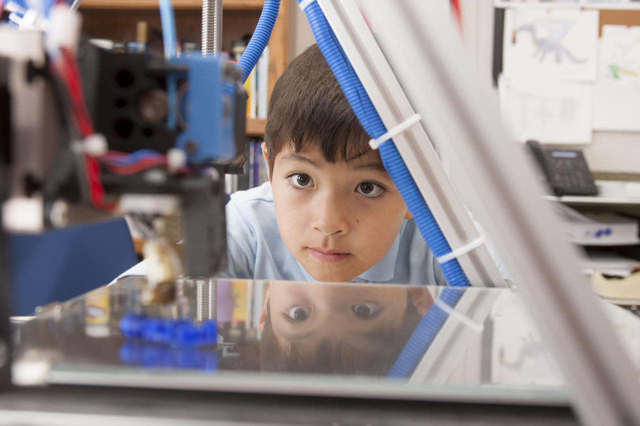 Boy looking at 3D printer