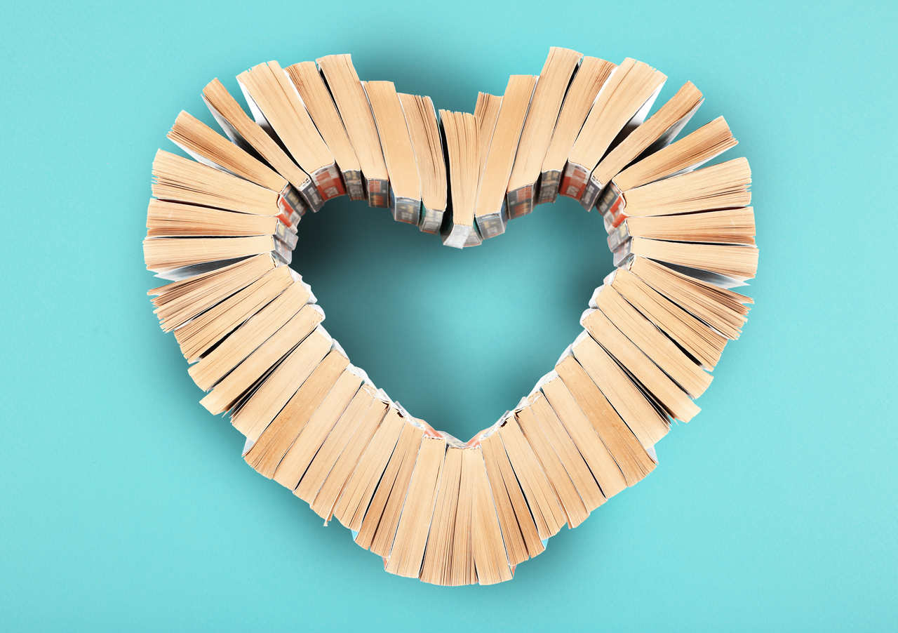 heart made out of books on a light blue background