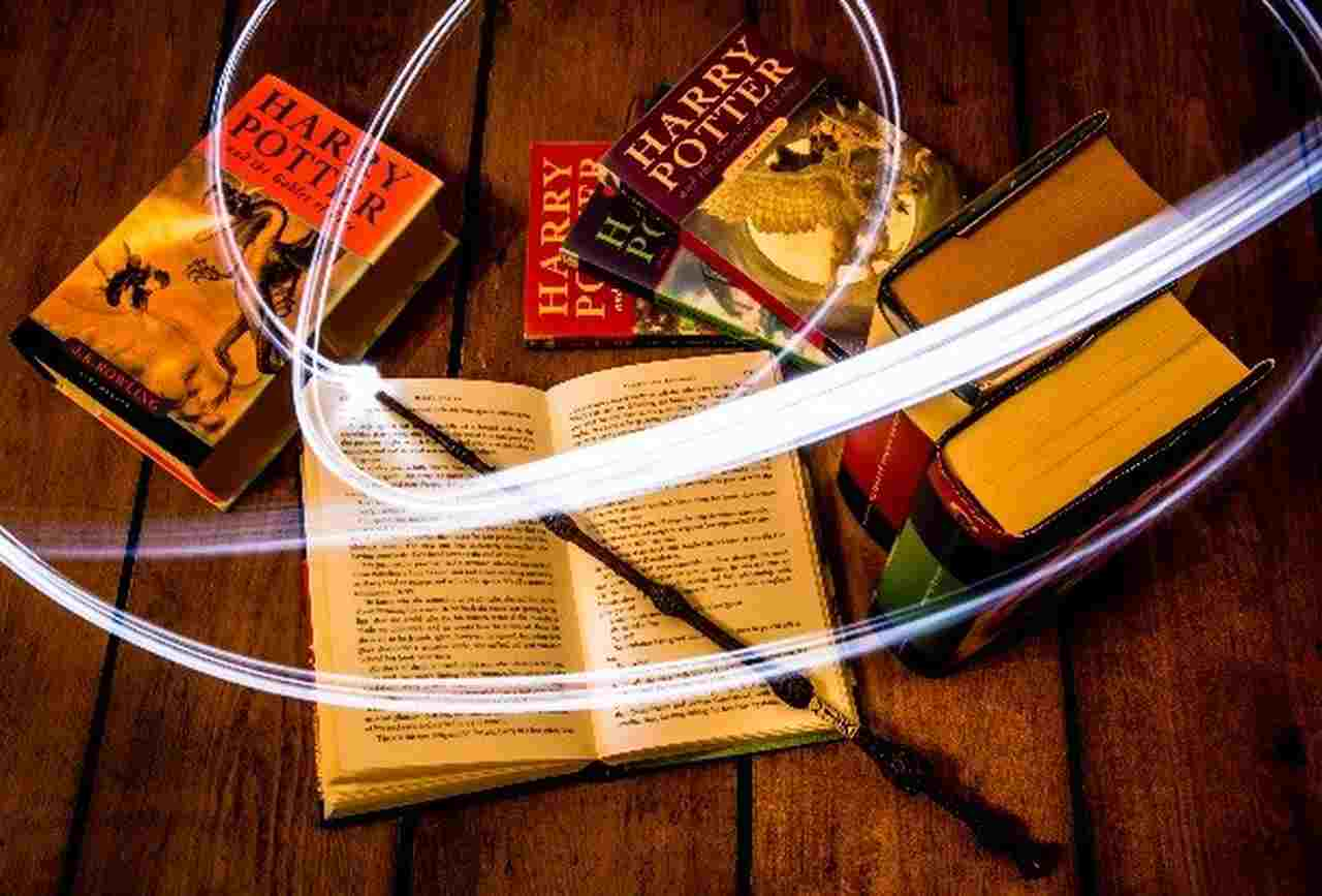 Harry Potter Books open on wooded table with wand